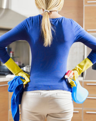 Woman cleaning her kitchen with a rag and disinfectant spray